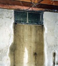 Flooding through basement windows in a Clay home.