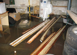 A severely flooding basement in Oneonta, with lumber and personal items floating in a foot of water