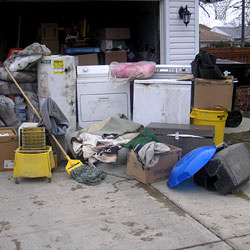 Soaked, wet personal items sitting in a driveway, including a washer and dryer in Oswego.