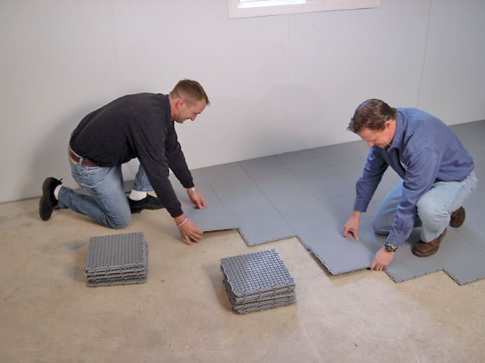 Merveilleux ... Contractors Installing Basement Subfloor Tiles And Matting On A  Concrete Basement Floor In Watertown, New